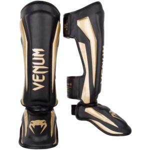 Zwart gouden scheenbeschermers van Venum Elite.